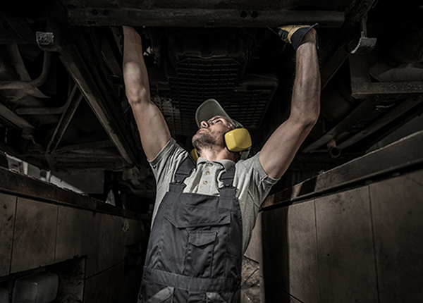 Male mechanic working on a commercial bus